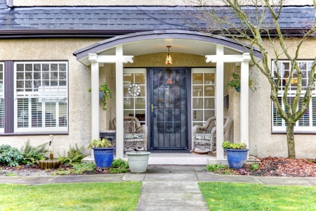 front porch: cute old town home with centered black door and walkway Stock Photo