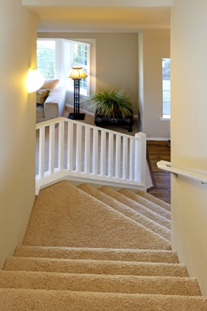 Cozy beige carpeted stairway and white railings Stock Photo - 25190272
