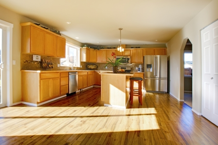 hardwood: Large kitchen room with wooden cabinets and steel appliances