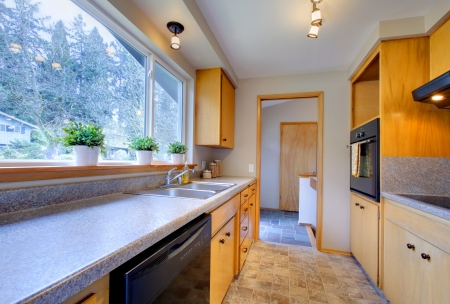 counter top: Modern kitchen with wooden cabinets, tile floor and wide window Stock Photo