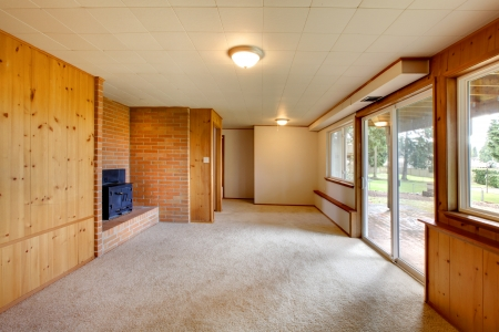 Empty living room with wood panel walls, cast iron fireplace, brick wall, carpet floor, glass sliding door photo