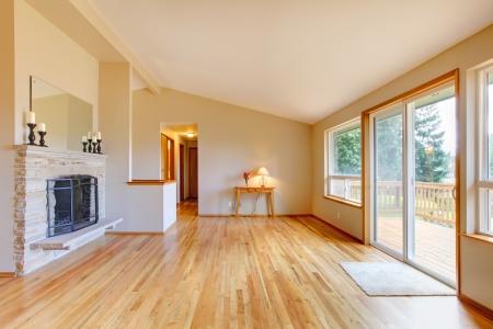 Leeres Wohnzimmer mit Kamin, Parkett und Glas-Schiebe-Tür Ausgang zum Deck