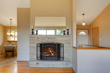 fireplace: Light warm tones fireplace with a beige background in a bright comfortable living room Stock Photo
