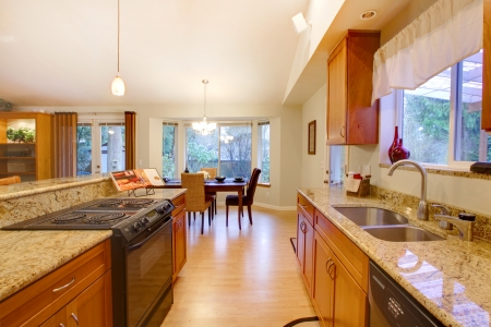 Bright kitchen room with wooden cabinets and hardwood floor. Dining room photo