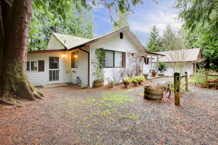 One story white northwest siding house with flower pots and garage Stock Photo - 25190476