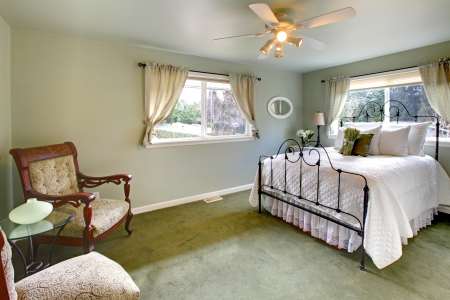 iron curtain: Olive tones bedroom with antique iron frame bed, green carpet and aristocratic chairs Stock Photo