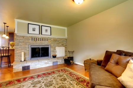 Living room with stone background fireplace, hardwood floor and velvet couch photo