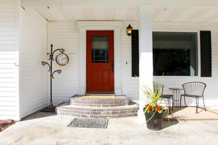 Classic simple porch with a contrast red wooden door and brick stairs photo
