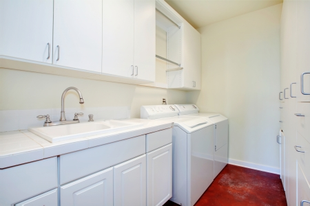 White laundry room with a red floor and white wooden storage combination Stock Photo - 25274588