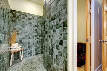 Great combination of green tile floor and walls, wooden doors and rustic table for towels. Small bathroom photo