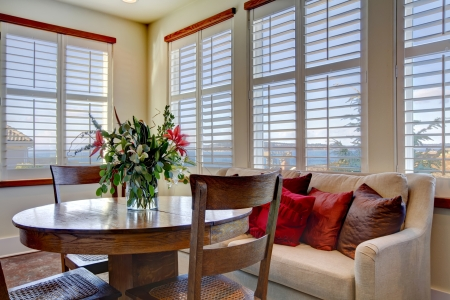 windows: Light tones beautiful dining area  with a rustic dining table set, beige sofa and bright red pillows