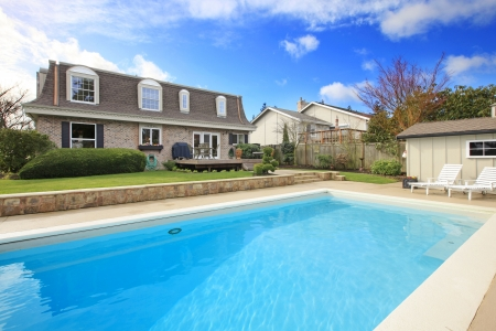 Two story stone facing house with back porch and big swimming pool photo