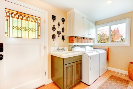 dryer  estate: Old-fashined laundry room with a rustic cabinet and rug on the floor
