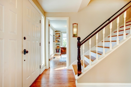 Bright hallway with wooden light brown stairs and whiskey color hardwood floor photo