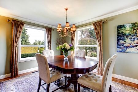 Olive tones dining room with old-fashined dining table set, chandelier, curtains and carpet