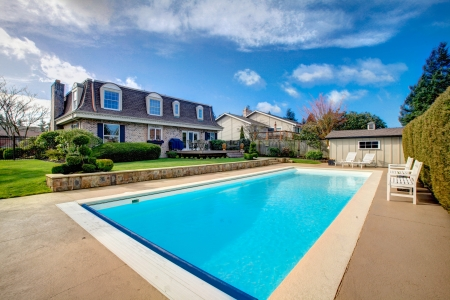 Two story stone facing house with back porch and big swimming pool
