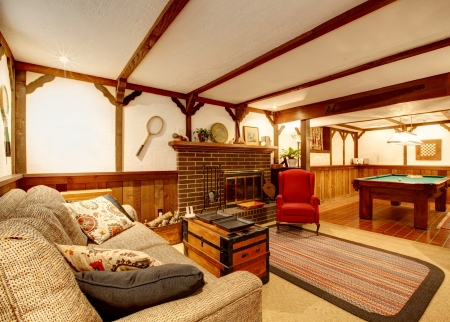 Cozy living room with ceiling beams, rustic couch, rug, wooden paneled walls, stoned background fireplace and pool table