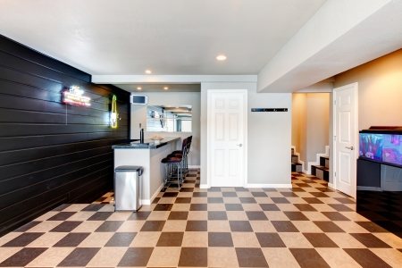 Entertainment room with bar, stools, aquarium. White coffered ceiling, mocha and brown concrete floor photo