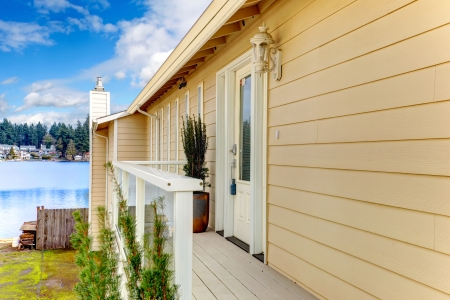 house siding: Wood deck with white railings overlooking beautiful lake Stock Photo