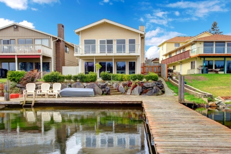 Paneled two story house with glass balcony  Backyard view from dock photo