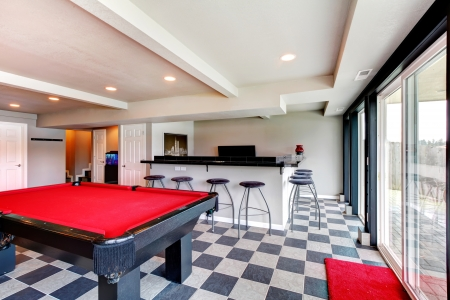 Bright entertainment room with coffered ceiling, concret floor, floor-to-ceiling window, bar, fireplace and pool