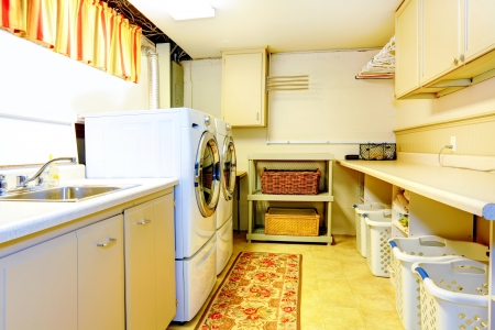 Big old style laundry room with modern appliances and wicker baskets photo