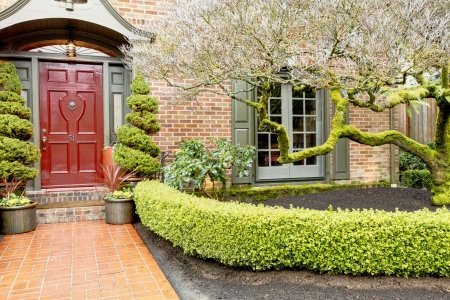 red door: Brick house with large windows and exterior shutters, red wood door, stoned walkway, trim hegde, exotic trees Stock Photo