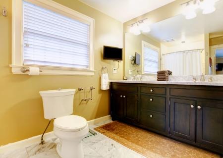 Badkamer met licht bruin behang oude wastafelmeubel en spiegel