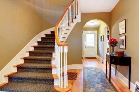 木製階段、素朴な黒のキャビネットと青敷物と温かみのある色調の廊下