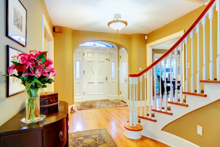 Yellow and white entrance hall with archway and spiral staircase photo