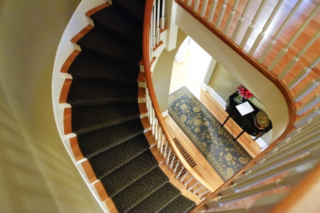 Wooden spiril staircase with carpet photo
