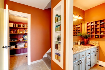storage: Small rust and white hallway with designed built-in shelves. Storage room and bathroom entrance