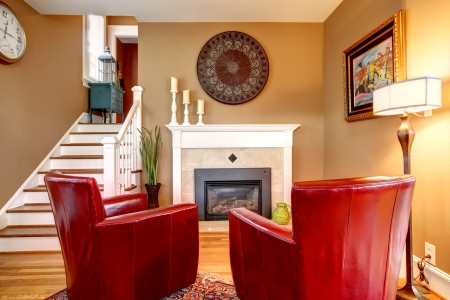Classic designed family room with comfortable red chairs, light tones fireplace, hardwood floor and beige walls photo