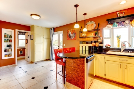 Small kitchen room with yellow wooden cabinets  rust walls and beige  tile floor photo