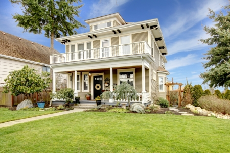front of: Classic american house with column porch and beautiful front flowerbed and trim