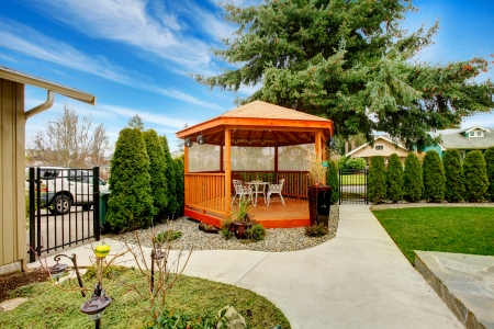 Classic wooden garden house on the backyardd naturally match with trees, flowerbed and trim Stock Photo - 25483789