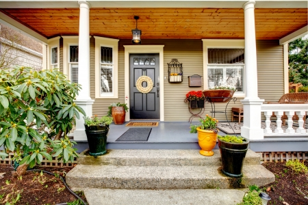 Column porch with wooden ceiling, black door, khaki paneled walls, flower pots photo
