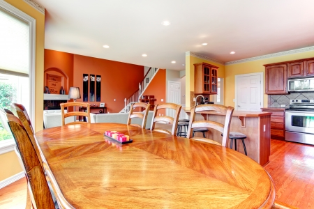 Interior design for kitchen, dining and livign room combination. Yellow walls of kitchen and dining room match weell with orange color of living room Stock Photo
