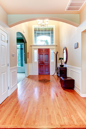 Soft colors hallway with hardwood floor, arch, high ceiling and cabinets photo