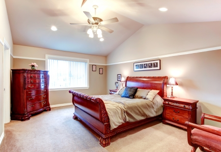 Beige bedroom with cathedral ceiling, carpet floor and great carved bed frame and storage cabinets photo
