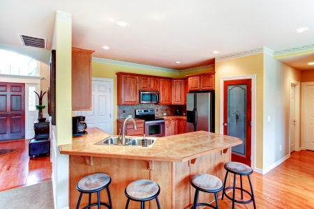 Yellow small kitchen with hardwood floor, red wood cabinets photo