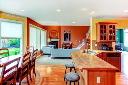 Interior design for kitchen, dining and livign room combination. Yellow walls of kitchen and dining room match weell with orange color of living room photo