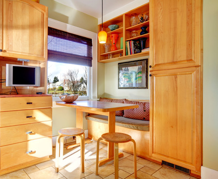 Kitchen room corner with light brown cabinets, small table and stools. photo