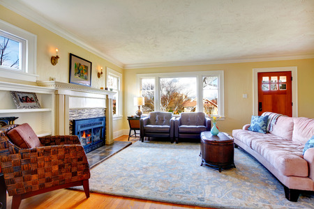 Bright living room with fireplace, soft couch, leather chairs photo