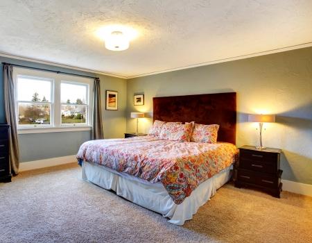 nightstands: Light blu bedroom with beige carpet, black wood nightstands and queen size red headboard bed Stock Photo
