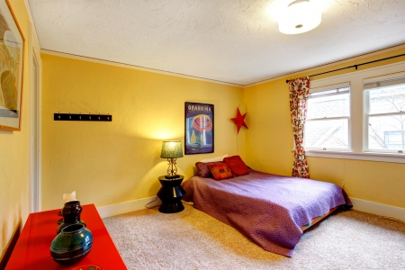Yellow wall bedroom with bright red cabinet  and queen size bed photo