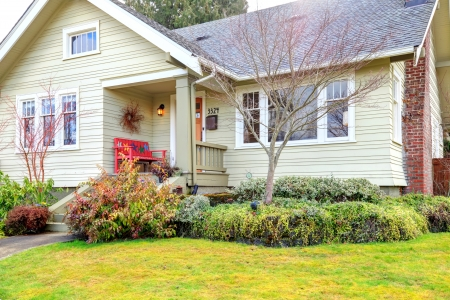 house siding: Siding house with column front porch and wood red bench