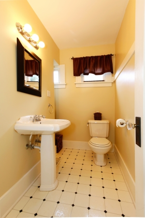 Yellow bathroom with designed tile floor, wood frame mirror and brown curtains Stock Photo