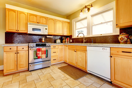 kitchen tile: Yellow kitchen with wood cabinets and dark brown backsplash design, tile floor and small rug