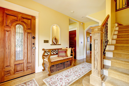 clean carpet: Yellow hallway with hardwood floor, stairs and rustic wood hallway storage seat Stock Photo